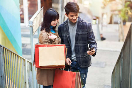 happy young asian couple looking at cellphone on the street while shopping in the city