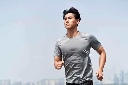 young asian man male runner jogger running jogging outdoors