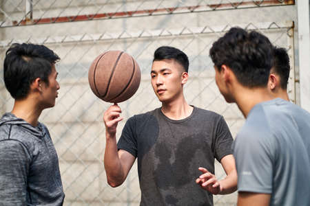 young asian adult men having fun playing with basketball outdoors