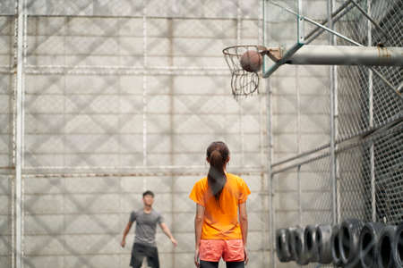 asian young man and woman playing basketball on outdoor court 免版税图像