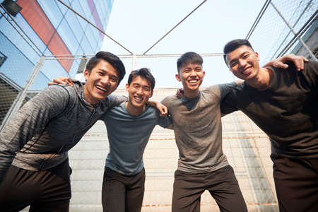 team of four young asian adult athletes having fun outdoors