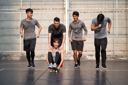 young asian adults men and woman having fun with skateboard outdoors 免版税图像