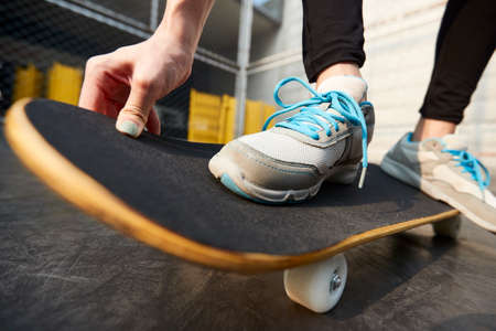 close-up shot of feet of a young asian woman skateboarding outdoors