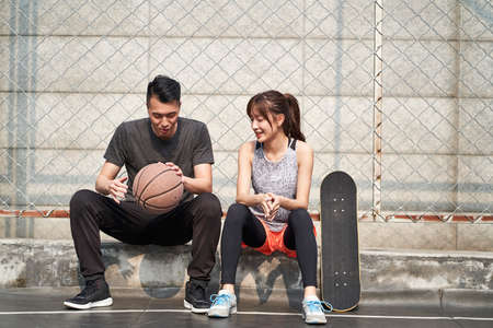 young asian adult male basketball player and female skateboarder sitting on court side talking chatting