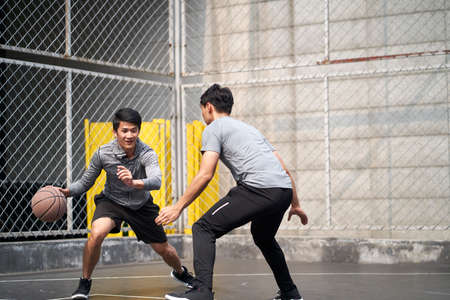 two young asian adult men playing one-on-one basketball on outdoor court