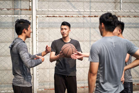 young asian basketball players chatting talking relaxing on outdoor court