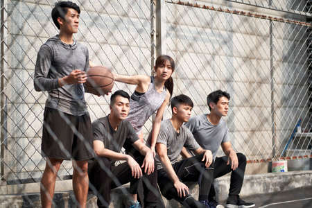 group of five asian young adults men and woman resting relaxing on outdoor basketball court 免版税图像