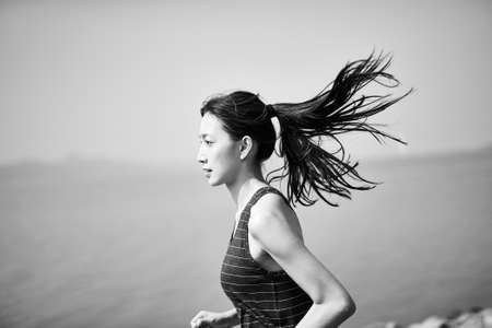 young asian adult woman running jogging outdoors by the sea, side view, black and white 免版税图像