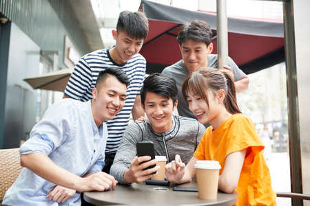 group of young asian adults four men and and a woman looking at mobile phone together outdoors
