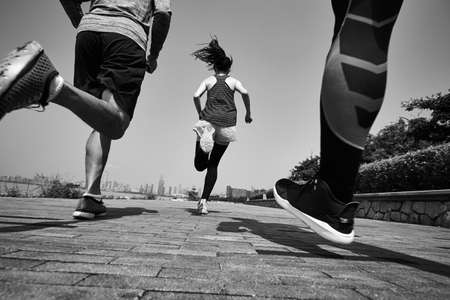 three young asian adults running jogging outdoors, rear and low angle view, black and white