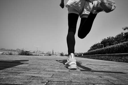 young asian adult woman running jogging outdoors, rear and low angle view, black and white