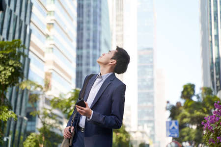 young corporate executive looking up at skyscrapers while walking in street in downtown of modern city