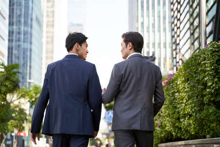 rear view of two asian corporate executives discussing business while walking in street in downtown of modern city 免版税图像