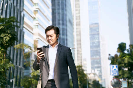 asian business man reading text message on cellphone while walking to work in cbd of modern city