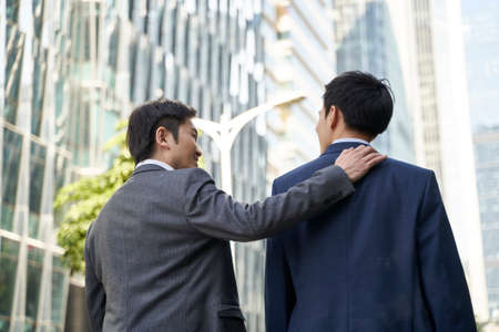 asian corporate executive giving subordinate a pat on the back while walking in street of central business district of modern city