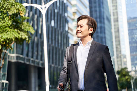 asian businessman walking to work in central business district in modern city