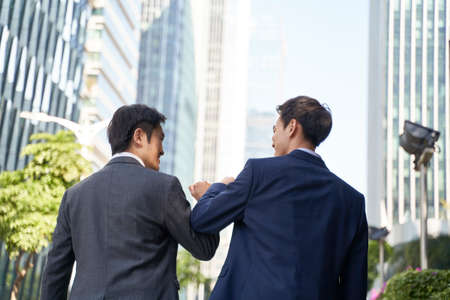 two asian business people bumping elbows celebrating success while walking in street in cbd of modern city