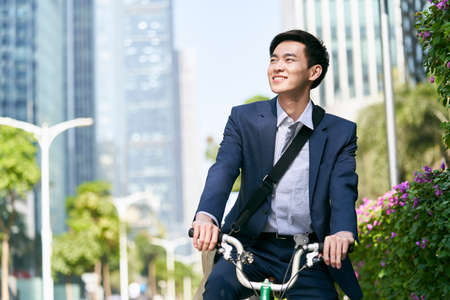 young asian business man riding bicycle in downtown financial district of modern city, happy and smiling