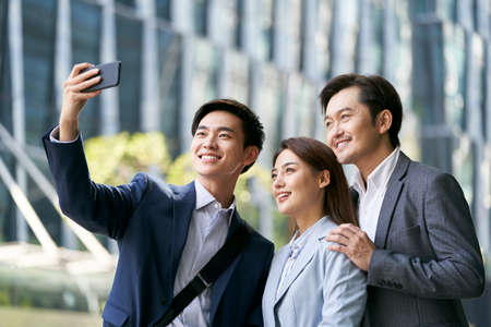 team of three asian businesspeople taking a selfie in downtown financial district of modern city