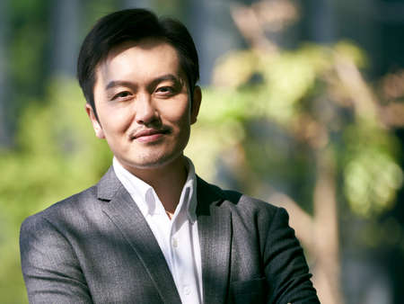 outdoor portrait of successful asian businessman looking at camera smiling