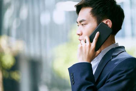 young asian businessman talking on cellphone outdoors 免版税图像