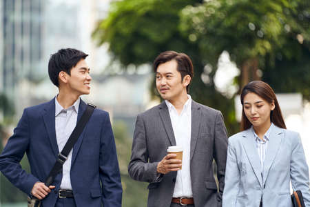 three asian business people walking talking on street