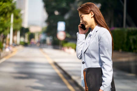 young asian female corporate executive talking on mobile phone while walking in city street 免版税图像