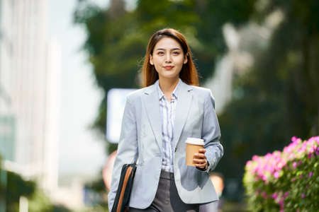 successful young asian female corporate executive walking on street holding a cup of coffee looking at camera 免版税图像
