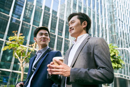 side view of two asian white collar office worker discussing business while walking in street in downtown of modern city