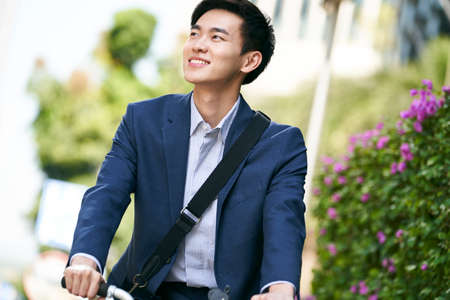 young asian business man riding bicycle to or from work, happy and smiling 免版税图像