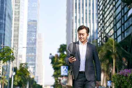 asian corporate executive looking at mobile phone while commuting to work in downtown of modern city 免版税图像