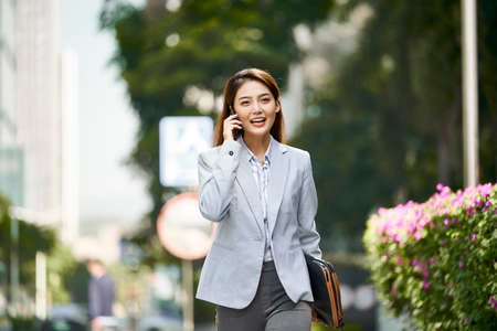 young asian female corporate executive talking on cellphone while walking in city street 免版税图像