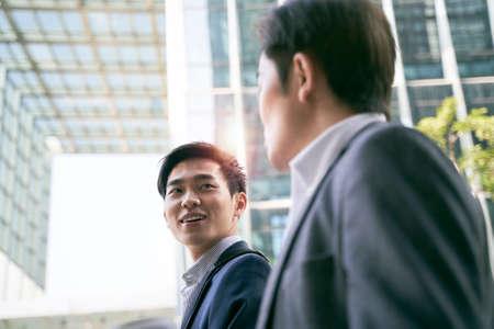 two asian business people walking talking on street in modern city 免版税图像