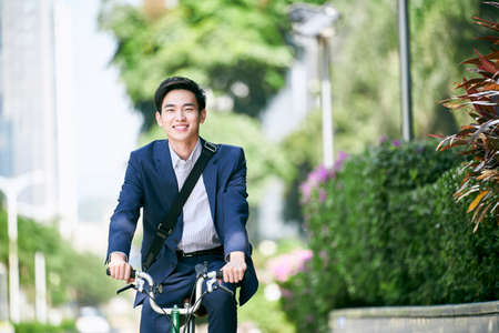 young asian business executive commuting by bike happy and smiling 免版税图像