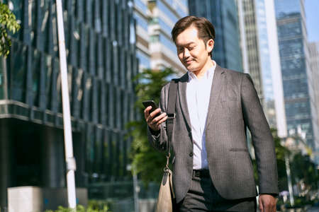 asian white collar office worker looking at mobile phone while walking to work in financial district of modern city