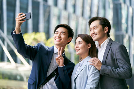 team of three asian business people taking a selfie outdoors in city financial district