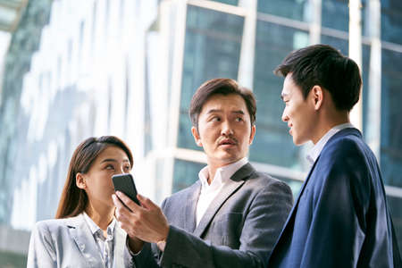 a team of asian business people standing in street having a discussion using cellphone in city downtown