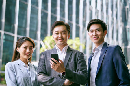 outdoor portrait of a team of three asian businesspeople looking at camera smiling