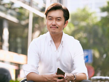 outdoor portrait of a successful asian businessman looking at camera smiling 免版税图像