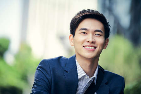 outdoor portrait of a successful asian business man happy and smiling
