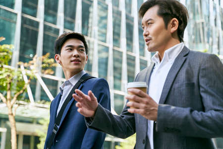 side view of two asian corporate executives discussing business while walking in street in downtown of modern city