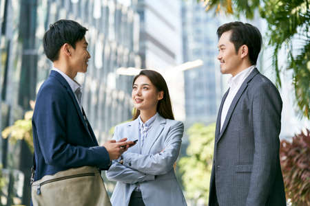 three asian business associates chatting in the street of downtown financial district in modern city