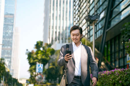 asian businessman looking at mobile phone while walking to work in cbd of modern city