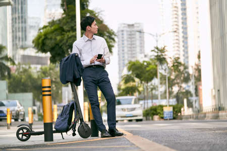 young asian businessman standing next to his electric scooter on street in downtow of modern city