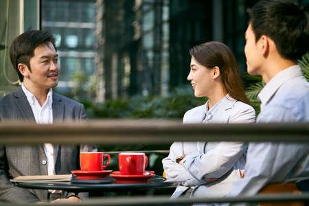 three asian businesspeople chatting in an outdoor coffee shop happy and smiling