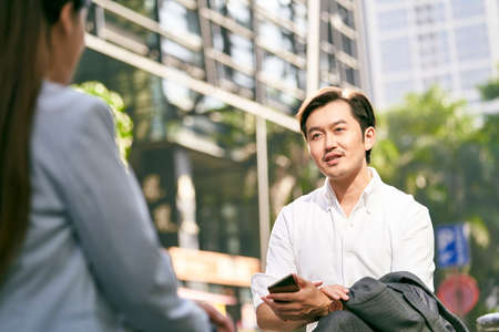 asian businessman and businesswoman conversing outdoors
