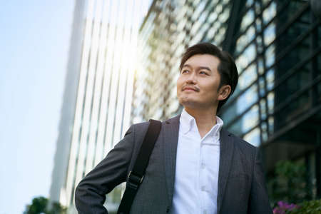 successful asian corporate executive walking in central business district of modern city