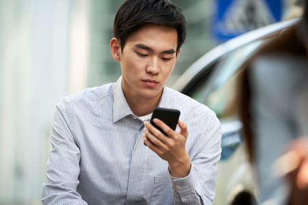 young asian office worker reading using cellphone outdoors