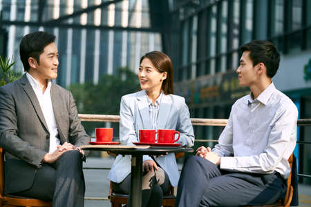 three asian corporate businesspeople discussing business outdoors in coffee shot