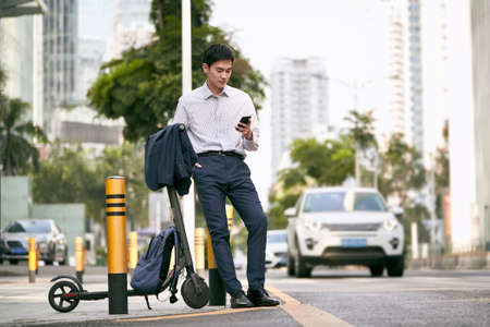 young asian businessman standing next to his electric scooter looking at cellphone on street in downtow of modern city